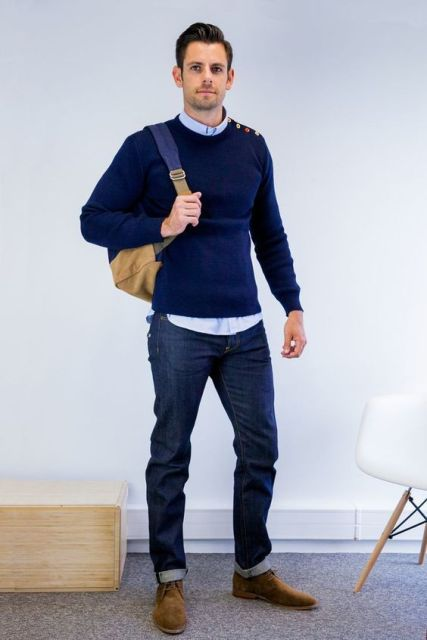 With light blue shirt, navy blue sweater, cuffed jeans and backpack