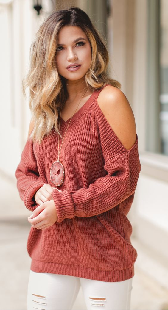 white ripped jeans, a red cutout shoulder sweater and a statement necklac