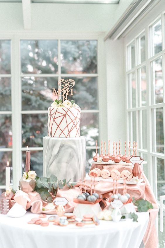 a modern wedding cake with a marble layer and a copper geo one with a geometric topper
