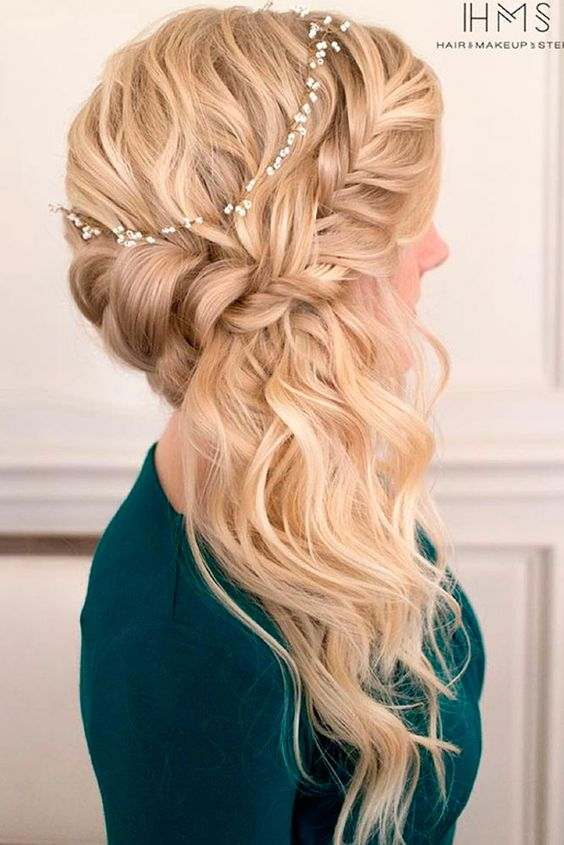 a side braided half updo accessorized with a small flower branch