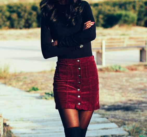 a black long sleeve top, a burgundy velvet mini skirt with a row of buttons and black suede tall boots