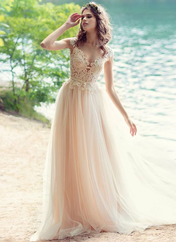 a champagne wedding dress with an illusion neckline, cap sleeves, lace appliques and a flowy skirt