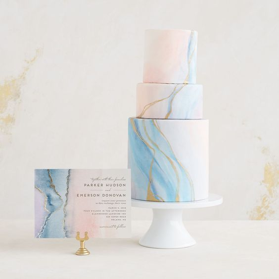 a romantic light blue and pink marbleized wedding cake with gold leaf and a matching card