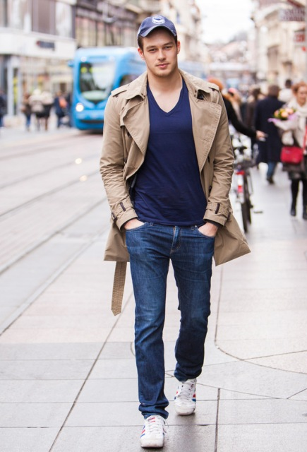 With navy blue t-shirt, jeans, white sneakers and beige trench coat