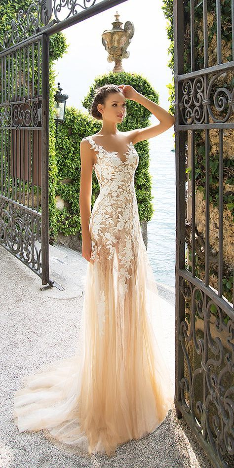 a champagne wedding dress with an illusion neckline lace appliques, a sheath silhouette and a small train