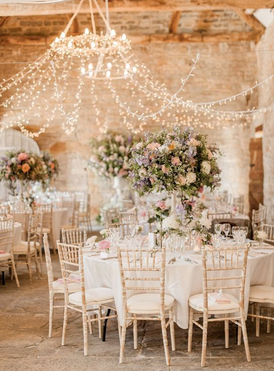 a beautiful canopy of lights for a barn wedding looks chic and brings enough light