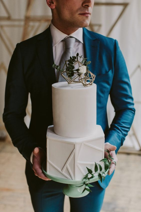 a white wedding cake with a textural geometric layer and some himmeli ornaments on top