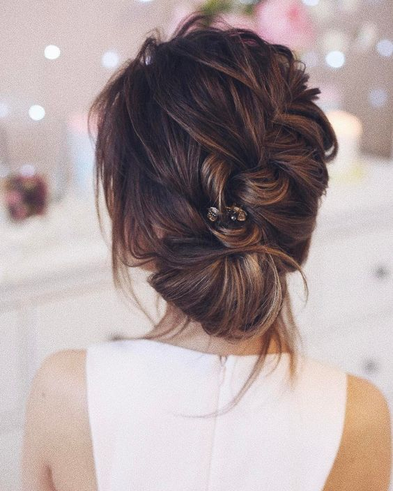 a messy diagonal braid updo with bangs and a rhinestone hair pin