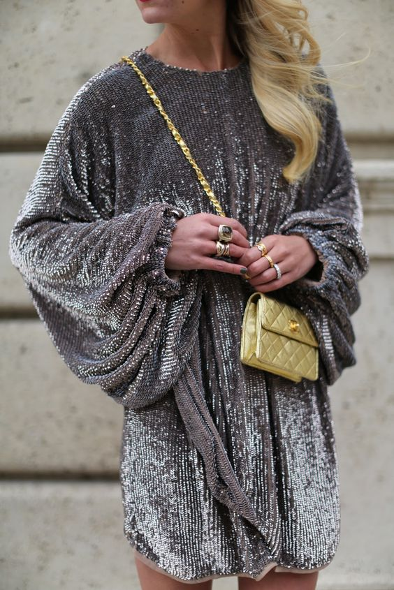 a grey sequin mini dress with wide sleeves, a high neckline and a sash