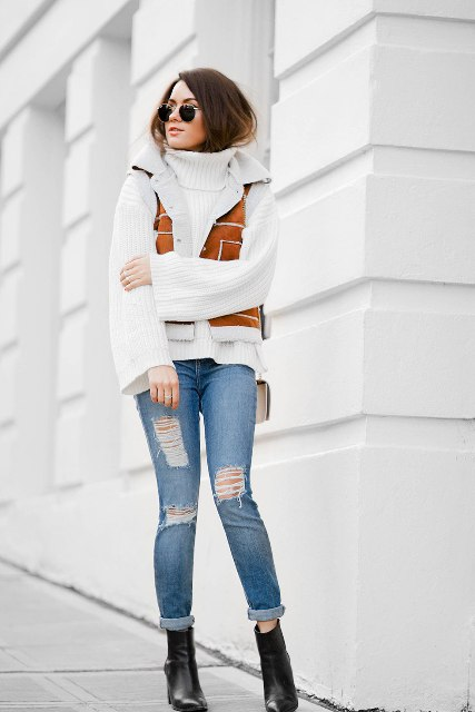 With white turtleneck sweater, distressed cuffed jeans and black leather boots