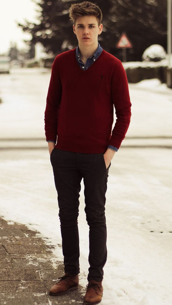 black pants, a denim shirt, a red sweater over it and brown shoes for an effortlessly chic look