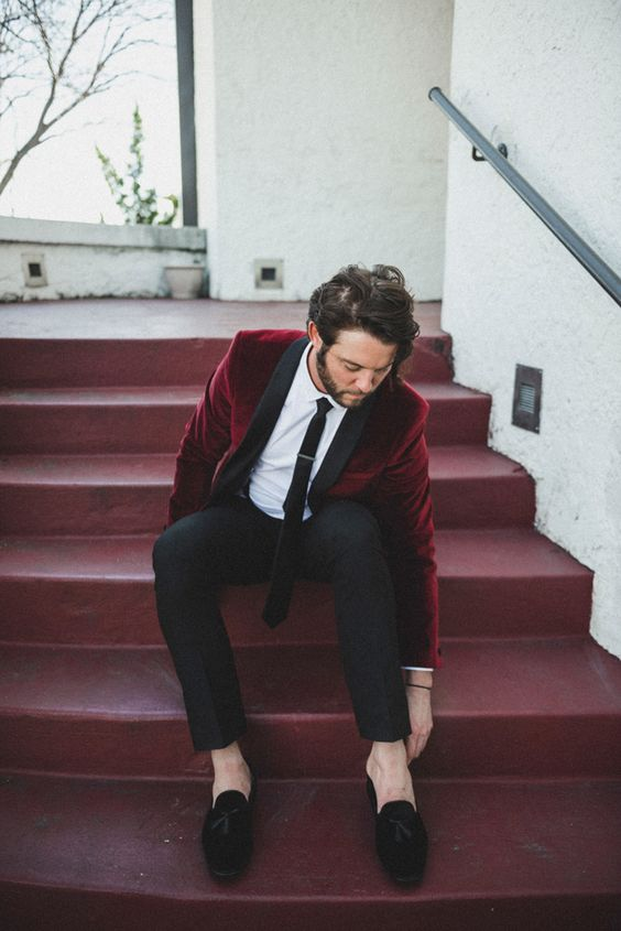 a trendy groom's look with black trousers, a white shirt, a black tie, a burgundy velvet jacket and black velvet loafers