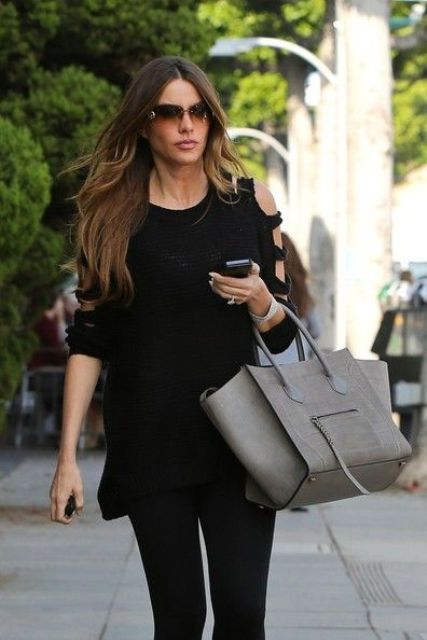 black leggings and a cutout shoulder black sweater is a simpel and cool combo