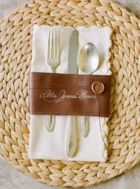 a leather cutlery and napkin ring with a seal and a wicker charger for a chic look