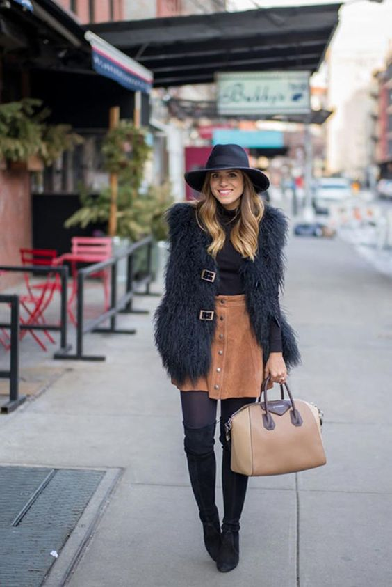 tall suede boots, a rust mini skirt, a faux fur vest and a black turtleneck