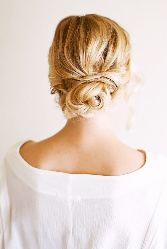 a messy, wavy twsited low bun with all hair up
