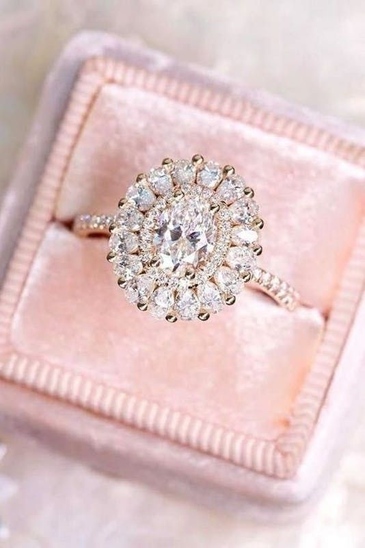 an oval-shaped diamond engagement ring with several halos for more bling