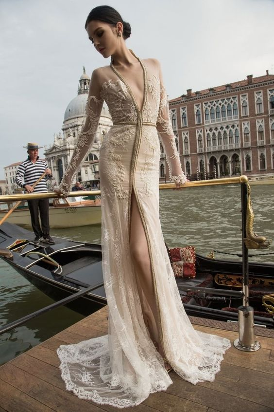 Inbal Dror wedding dress with long sleeves, a plunging neckline and a high front slit and a small train, illusion detailing