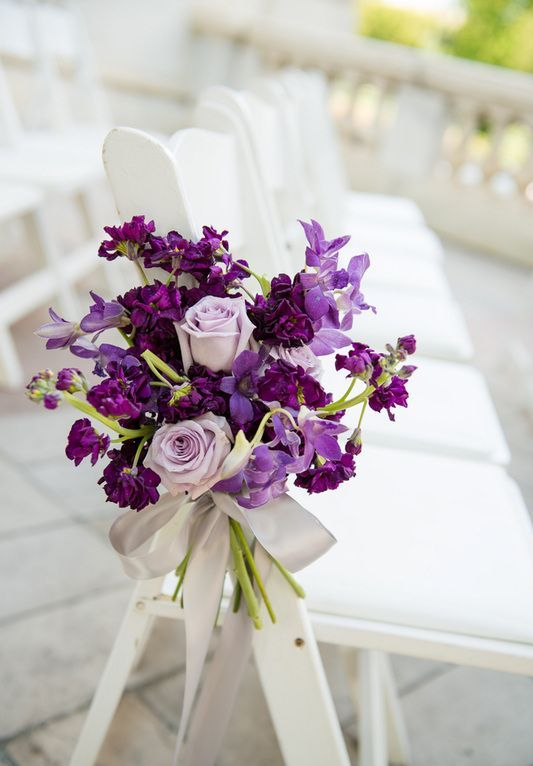 decorate the aisle chairs with gorgeous bouquets with violet and lilac blooms with a grey ribbon bow