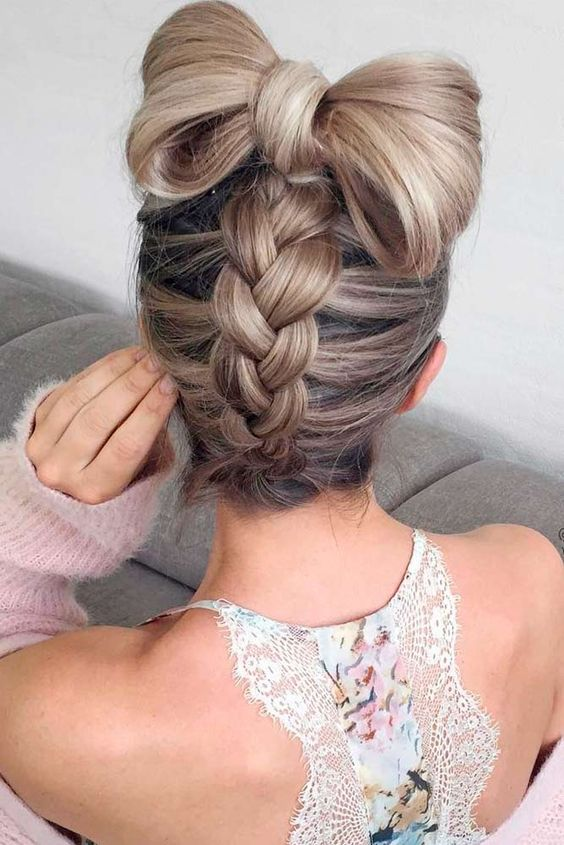 a fun braided updo with a large hair bow on top for a whimsy look