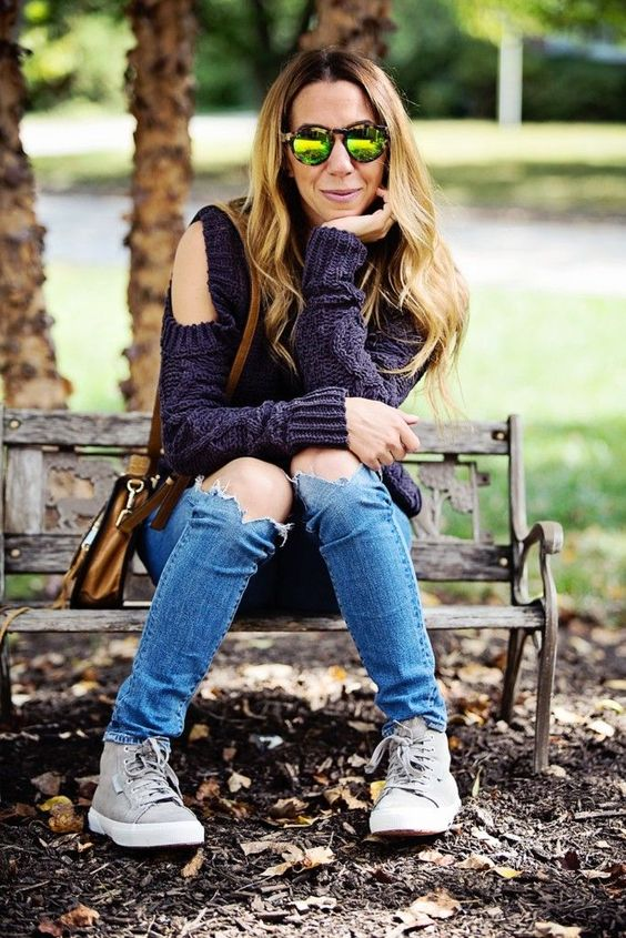 blue ripped jeans, a deep purple cable knit sweater with a cold shoulder and greey sneakers