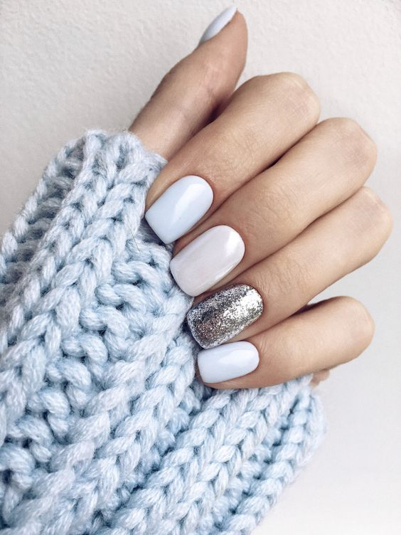 white nails with a silver leaf accent nail look very elegant and winter-like