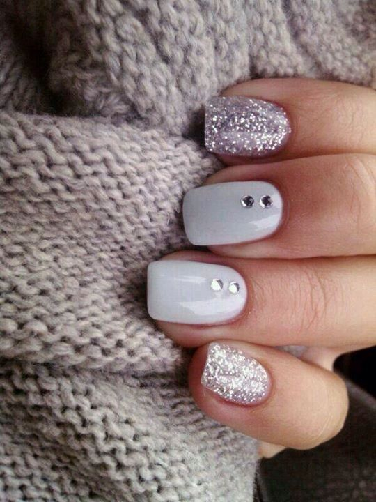silver glitter manicure with two white ones and rhinestones on them