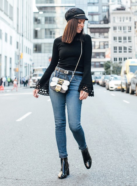 With black blouse, skinny jeans, black boots and unique bag