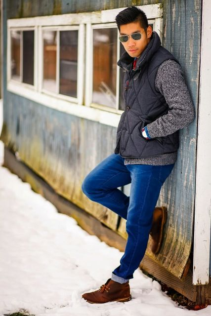 With gray sweater, black puffer vest and cuffed jeans