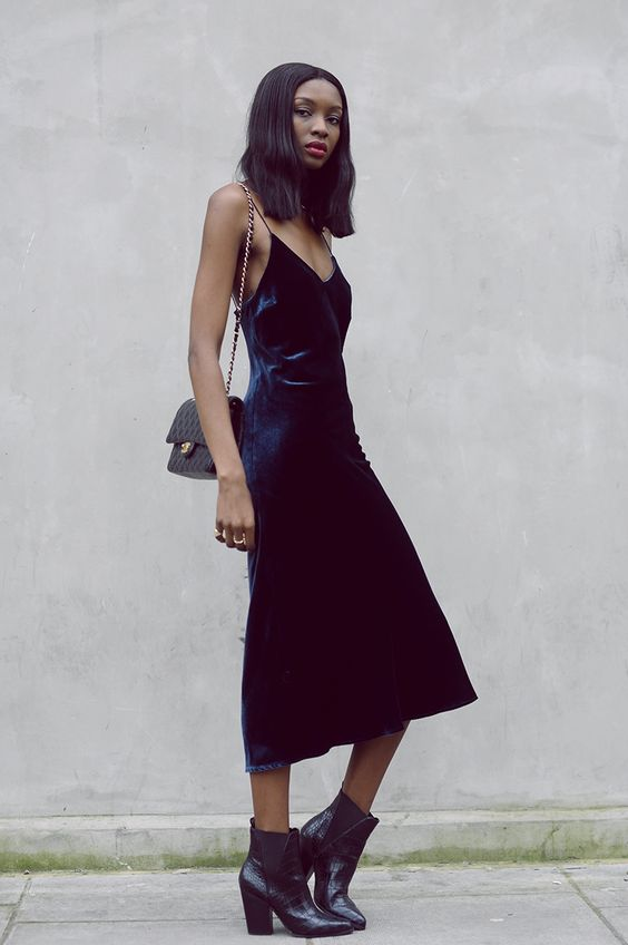 a navy velvet slip dress, black chelsea boots and a black clutch