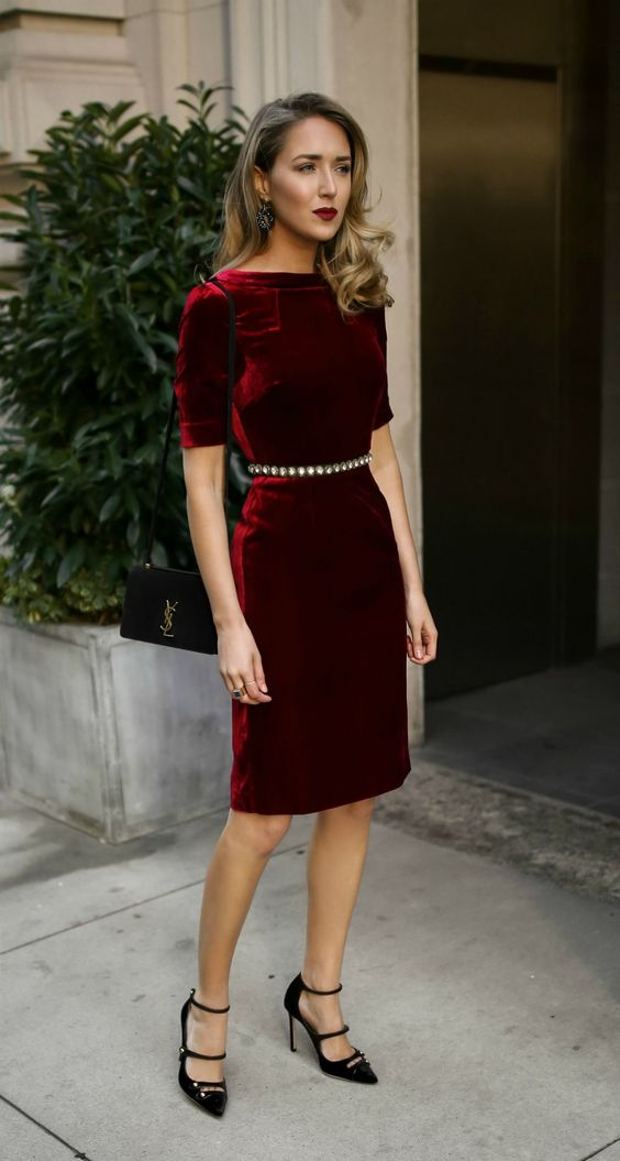 a burgundy velvet over the knee dress with short sleeves, a high neckline and an embellished belt