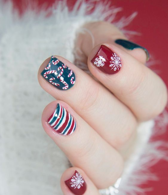 red, dark green and whiet nails with snowflakes, candy canes and stripes