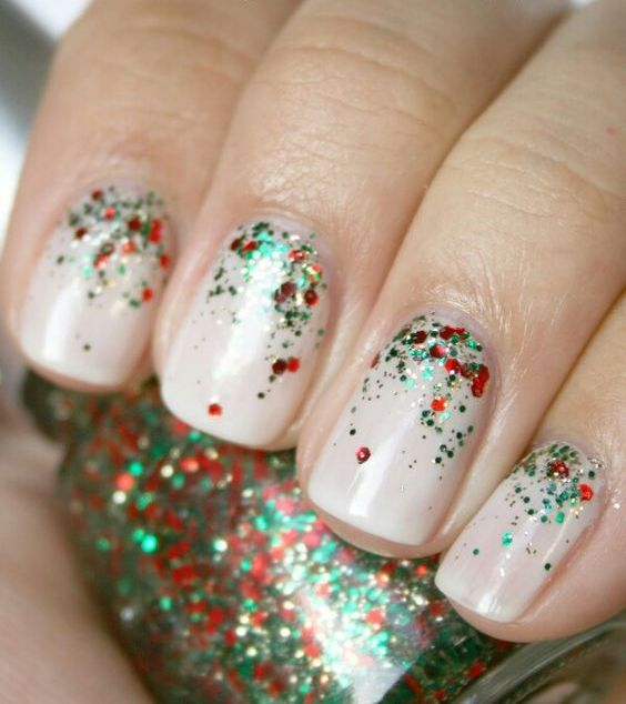 neutral nails with red, gold and emerald glitter on top