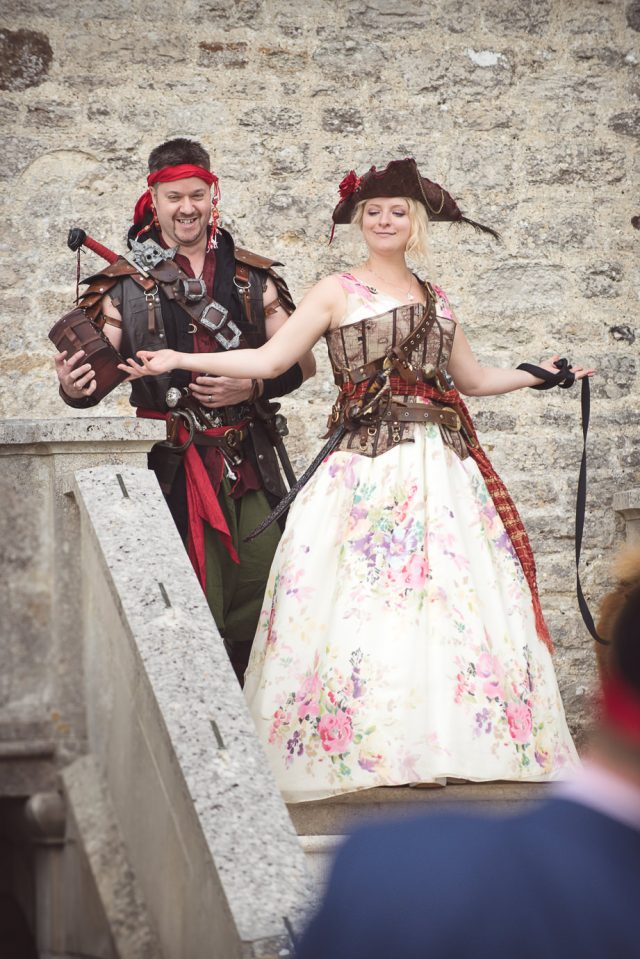 The bride was wearing a floral wedding dress and some pirate accessories, and the groom was dressed as a pirate