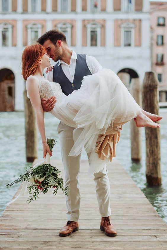a romantic wedding dress with a flowy layered skirt and a boho lace bodice, no sleeves for a Venice elopement
