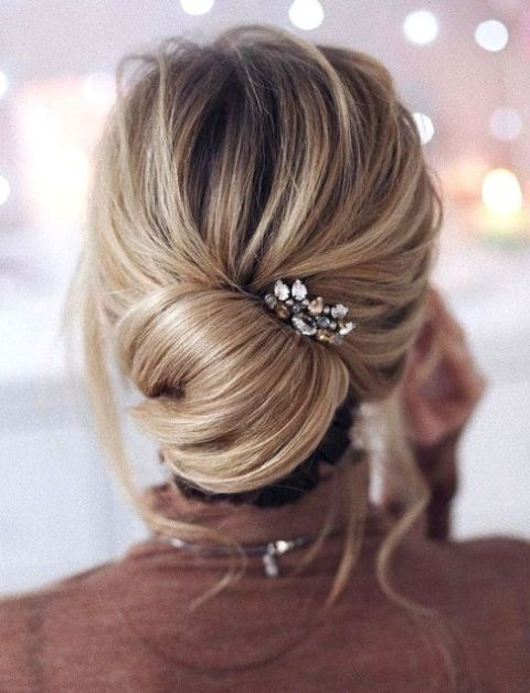 a messy low chignon hairstyle with bangs and a rhinestone headpiece