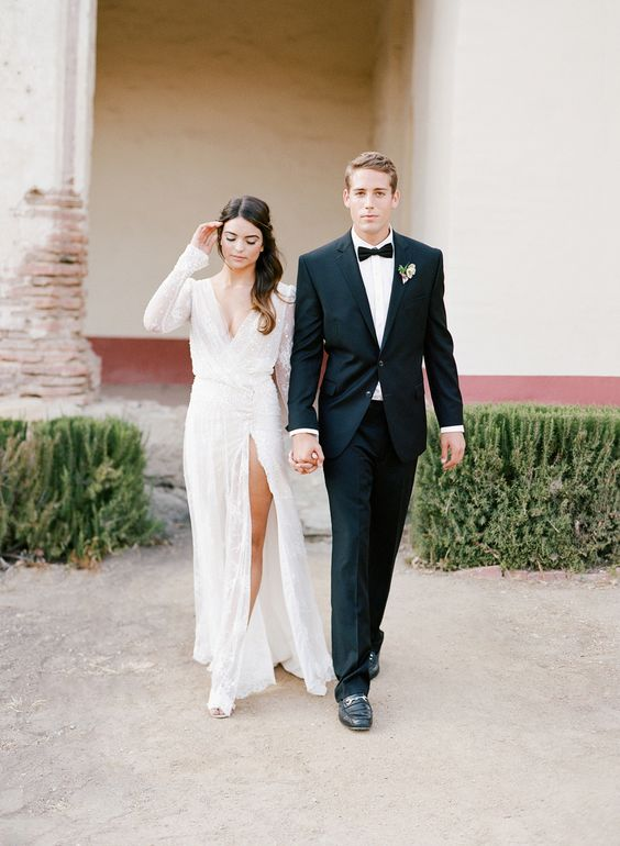 a modern sparkly wedding dress with long sleeves, a deep V-neckline and a thigh high slit