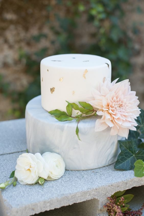 a modern wedding cake with a grey marbleized layer and a white gold leaf layer plus a large bloom