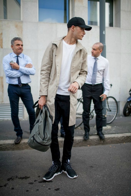 With white t-shirt, black pants, beige trench coat and gray backpack