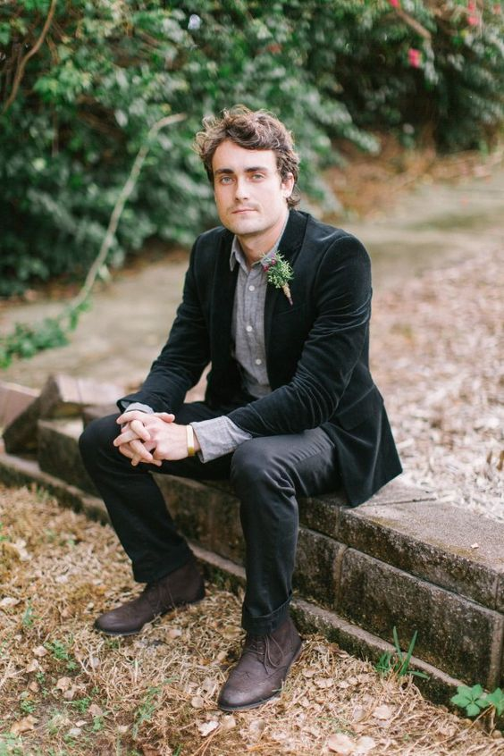 a relaxed groom's look with a grey shirt, black pants, brown boots and a black velvet jacket