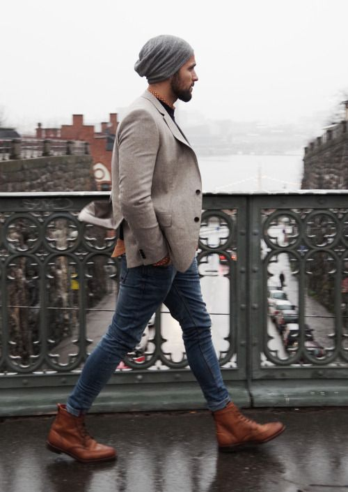 blue jeans, brown boots, a neutral blazer, a grey beanie for a casual look