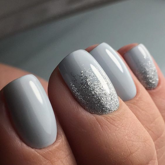 white nails with a touch of silver glitter for a chic wintery look