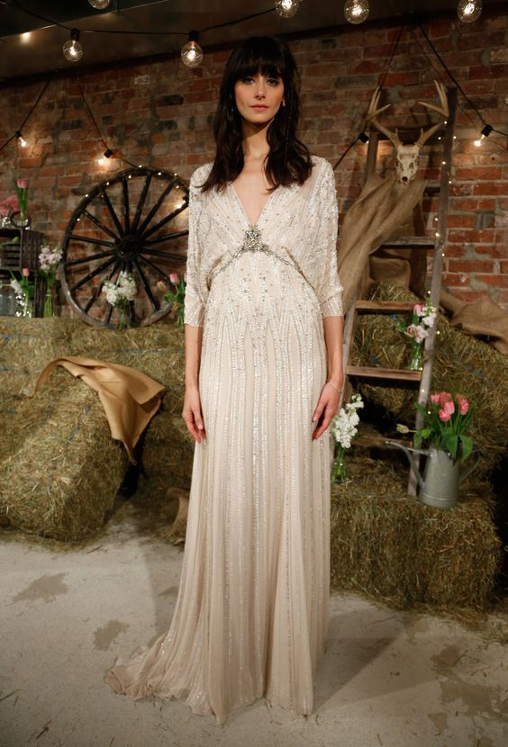 a heavily embellished wedding dress with long sleeves, a deep V-neckline shows retro glam