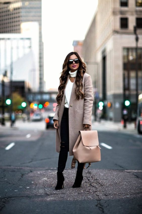black ripped jeans, a creamy cutout sweater, a blush coat and black boots