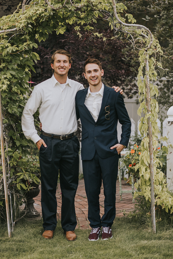 The groom was wearing a black suit with no tie and burgundy sneakers