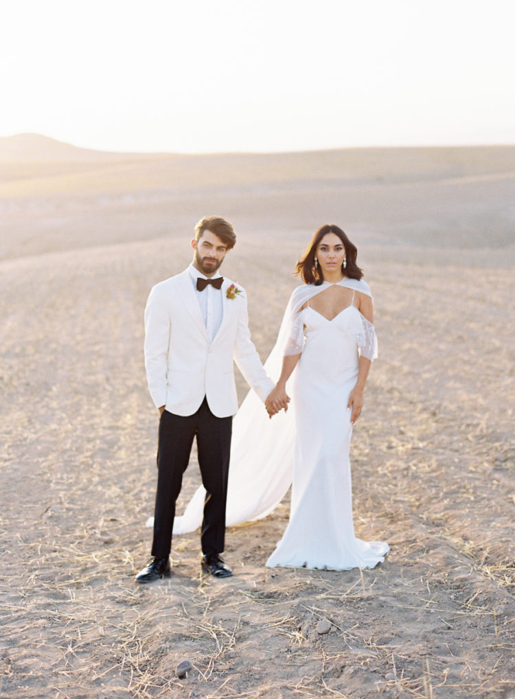 The first bridal look was done with a cold shoulder weddding gown and an airy cape, the groom was wearing a fresh take on a white tux