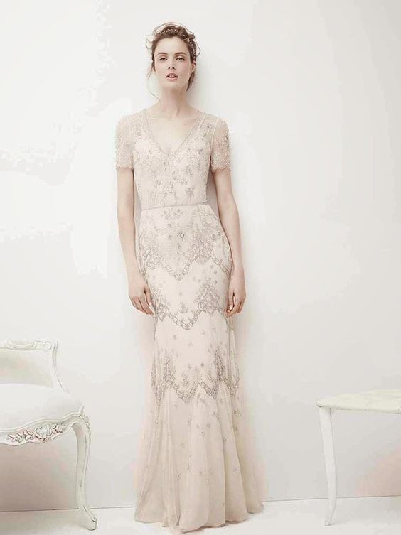 an embellished retro-inspired wedding dress with a V-neckline, short sleeves and delicate lace