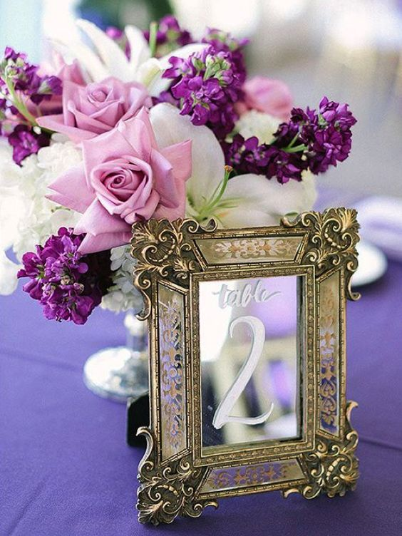 a centerpiece with pink roses, white and violet blooms and a vintage framed mirror