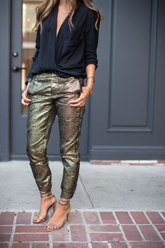 a black shirt with a plunging neckline and sparkly textural pants for a simple yet sexy look