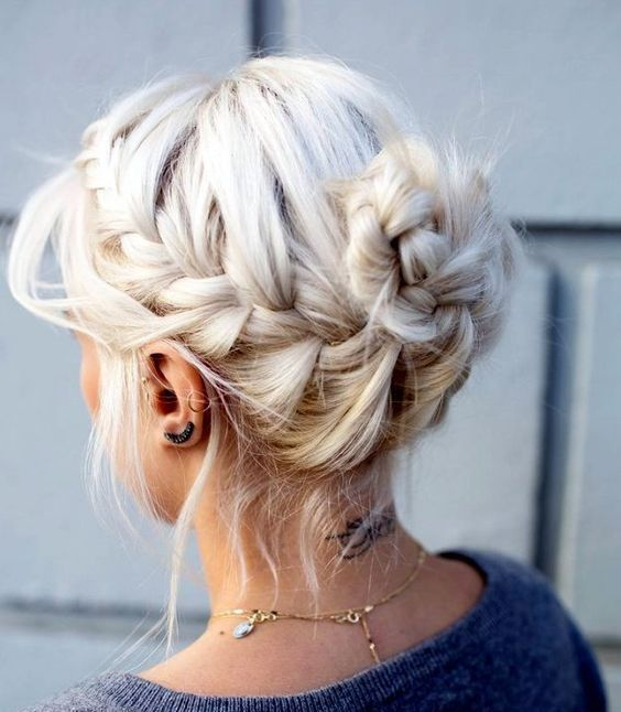 a classic messy braided updo with a bun and bangs hanging
